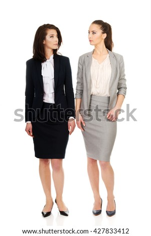 Two women in office outfits looking at each other. - stock photo