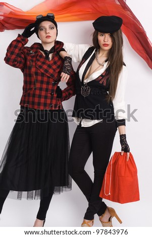 Two women in stylish red and black dresses. fashion photo - stock photo