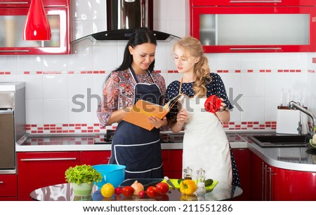Two women in the kitchen cook using cookbook  - stock photo