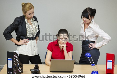 Two women in the office watching his girlfriend at work