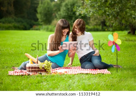 Two women in the park on a picnic with a Tablet PC - stock photo