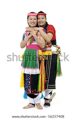Two women in traditional dress embracing and smiling