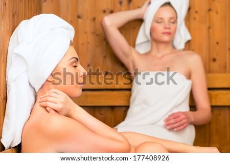 Two Women in wellness spa relaxing in wooden sauna - stock photo