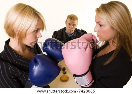 Two women lawyers wearing boxing gloves facing each other with a judge in background