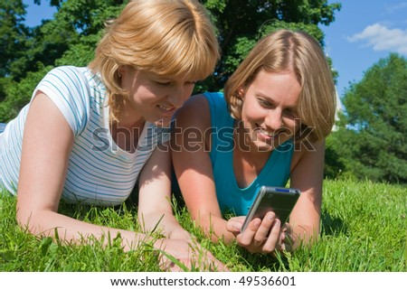 Two women look in the pocket computer
