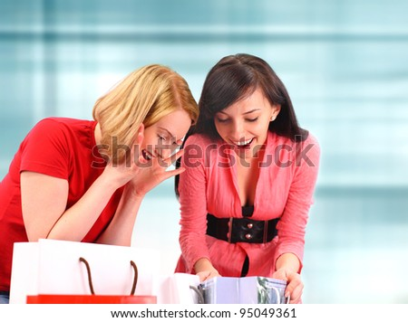 Two women looking in their shopping bags - stock photo