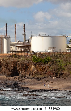 Two women looking on Glass Beach Kauai with refinery behind