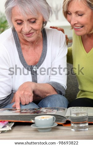 Two women looking through family photo album - stock photo