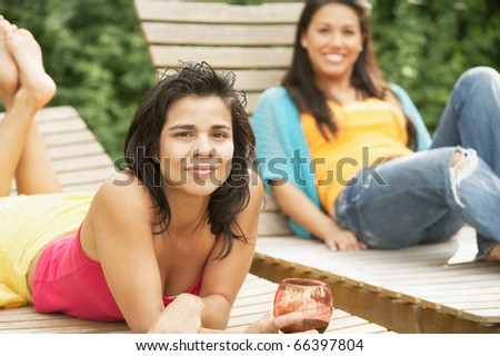 Two women lying on lounge chairs - stock photo