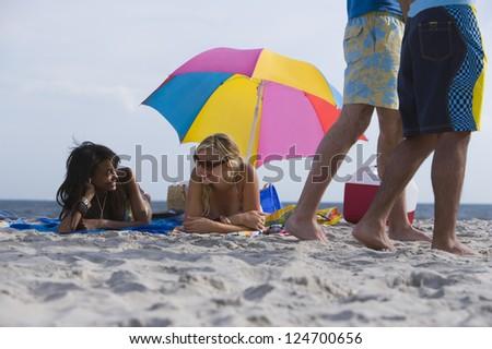 Two women lying on the beach while men walk around - stock photo