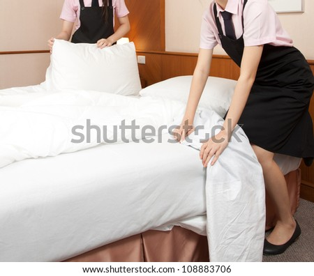 Two women maid making bed in hotel room - stock photo