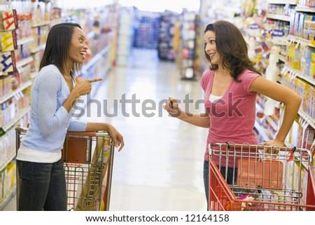 Two women meeting and chatting in supermarket aisle - stock photo