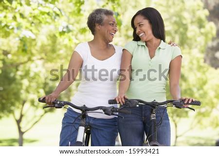 Two women on bikes outdoors smiling - stock photo
