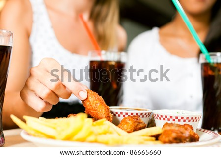 Two women - one is African American - eating chicken wings and drinking soda in a fast food diner; focus on the meal - stock photo