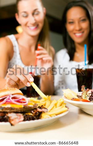 Two women - one is African American - eating hamburger and drinking soda in a fast food diner; focus on the meal