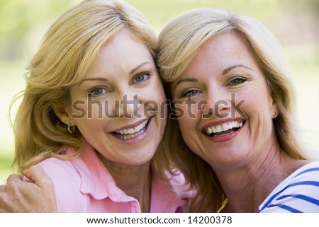 Two women outdoors embracing and smiling - stock photo