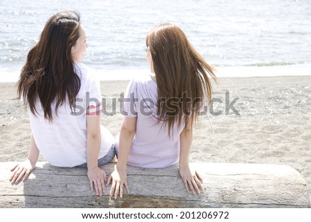 Two women overlooking the sea from the sandy beach - stock photo