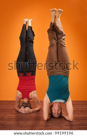Two women perform Sirsasana headstand positions over orange background - stock photo