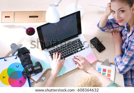 Two women photographers sitting on the desk with laptop