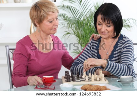 Two women playing chess and having a chat - stock photo