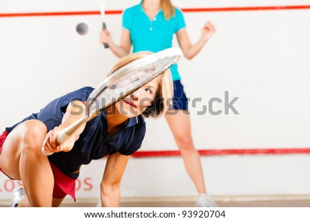 Two women playing squash as racket sport in gym, it might be a competition - stock photo