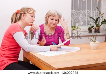 Two women pondering in living room over documents - stock photo