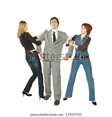 Two women pulling a man in opposite sides - stock photo