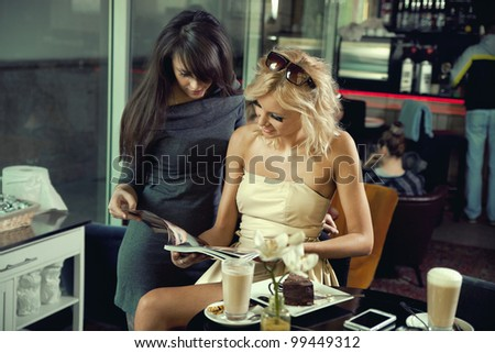Two women reading a newspaper - stock photo
