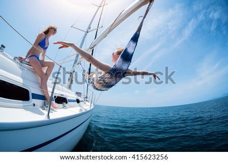 Two women relax on the sail boat moving in the sea - stock photo