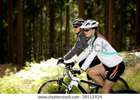 two women riding bikes through the forest