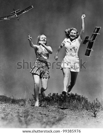 Two women running and playing with model airplanes - stock photo