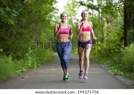 Two women running on a paved trail through the woods - stock photo