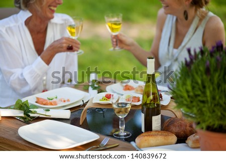 two women saying cheers at dining table outdoors - stock photo