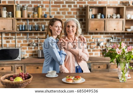 two women, senior and young having good time in kitchen