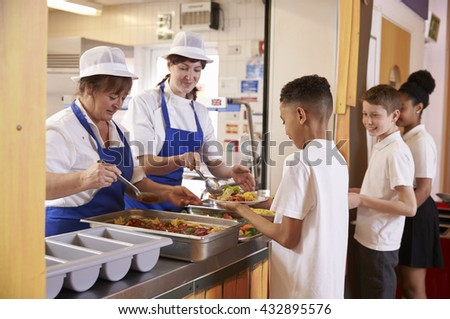 Two women serving food to a boy in a school cafeteria queue - stock photo