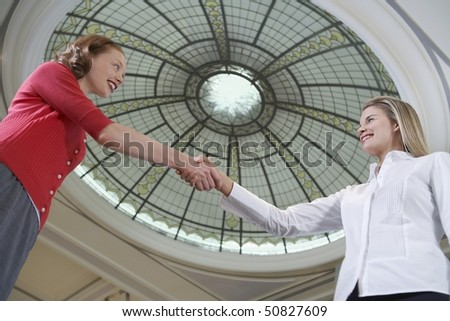Two women shaking hands under dome, low angle view