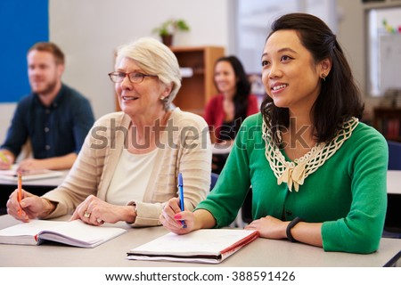 Two women sharing a desk at an adult education class look up - stock photo