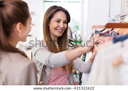 Two women shopping in a boutique - stock photo