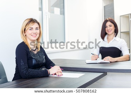 Two women sitting at a table in the office. Blonde and brunette on a job interview, or meeting.Business ladies at work