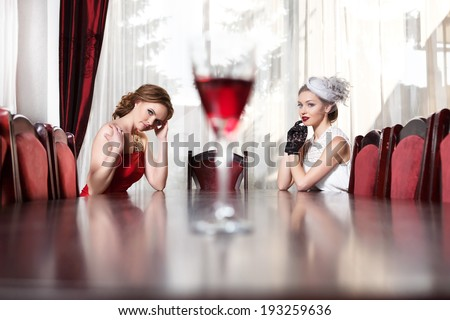 Two women sitting at table in restaurant. A glass of of red wine costs in the center of the table. - stock photo