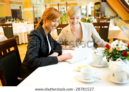 Two women sitting at table in restaurant. They're smiling and looking something on laptop. - stock photo
