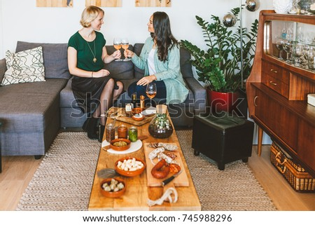 two women sitting on a sofa and having fun with a glass of wine and ready to eat food