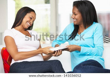 Two Women Sitting On Sofa Exchanging Gifts - stock photo
