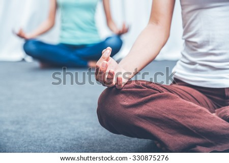 two women sitting on the floor with mediation gesture