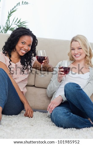 Two women sitting on the ground holding wine glasses are smiling at the camera - stock photo