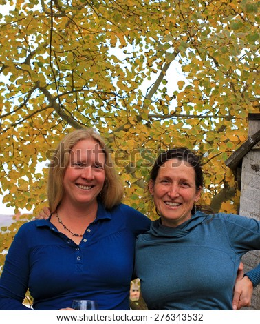 Two women smiling outdoors with autumn leaves in the background. - stock photo