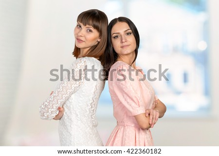 Two women standing back to back  - stock photo