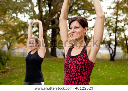 Two women stretching in a park - outdoor exercise - stock photo