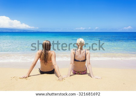 Two women sun tanning on a sunny beautiful beach. View from behind of women relaxing while on a beautiful island vacation - stock photo