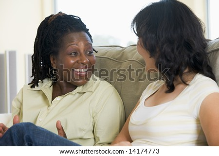 Two women talking in living room and smiling - stock photo